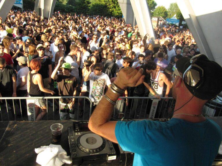 Menschen tanzen ausgelassen unter dem Expo-Kunstwerk im Parc Jean-Drapeau, Montréal