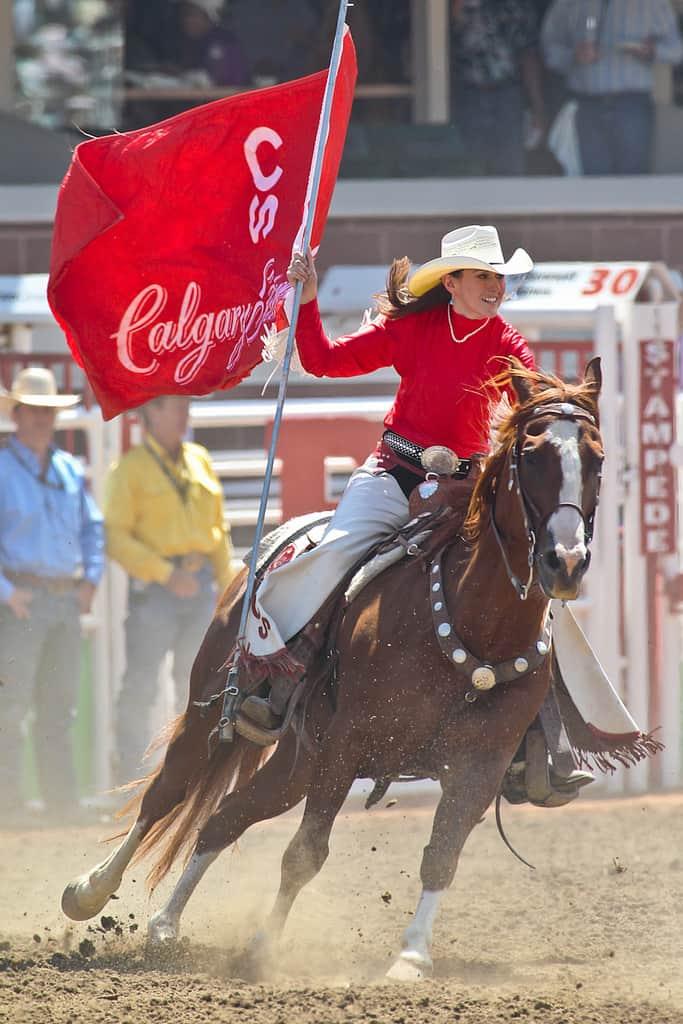 Reiterin trägt Calgary Stampede Flagge