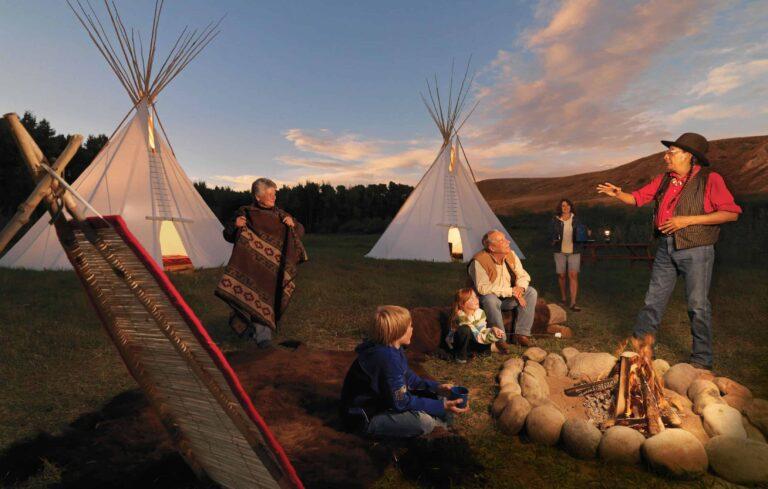 Traditioneller Geschichtenerzähler am Lagerfeuer im Tipi Village des Blackfoot-Crossing Historical Park