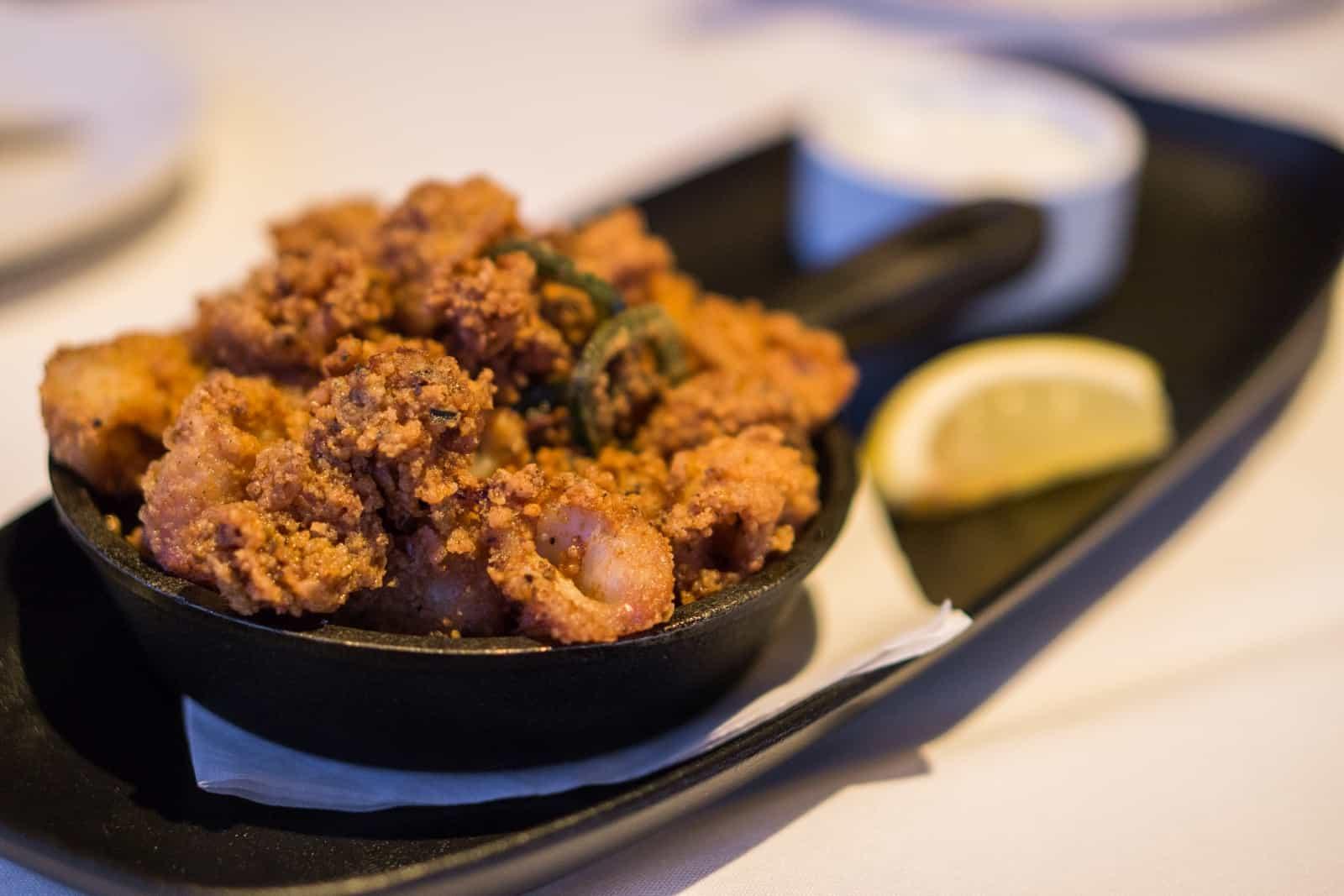 Eine weitere Vorspeisen-Leckerei, frittierte Calamari mit Tzatziki und Zitronenspalten. Foto