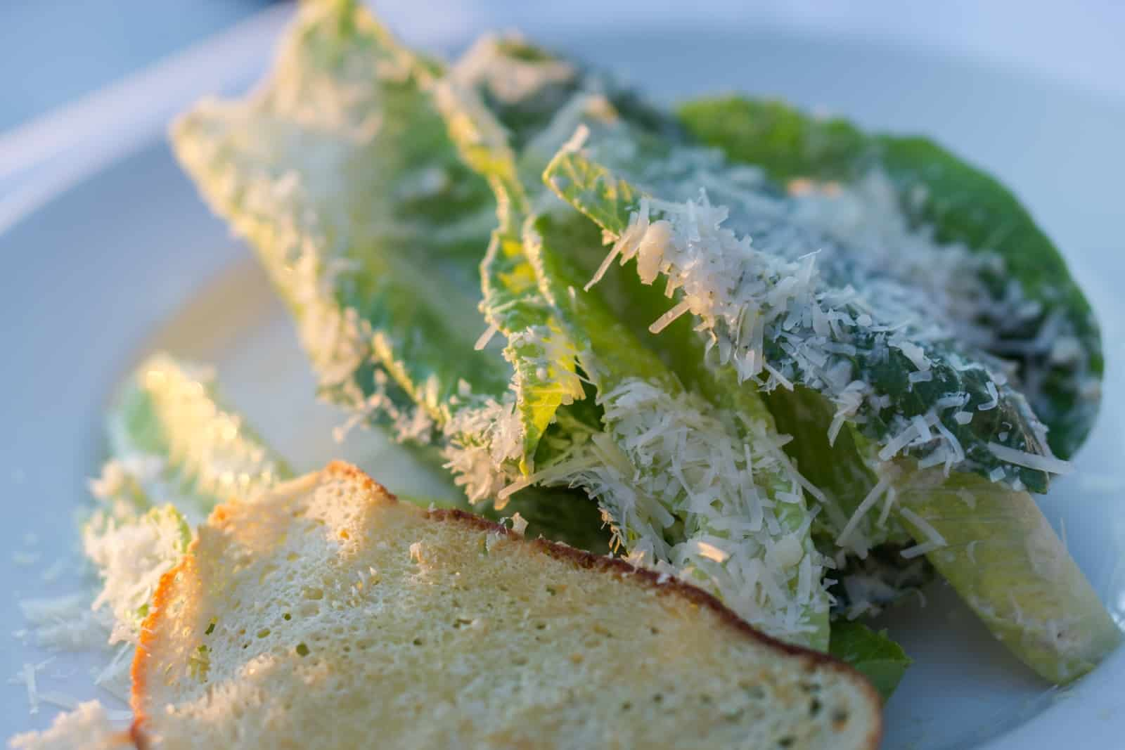 Caesar Salad mit Blättchen vom Grana Padano und Parmesan Crostini. Foto