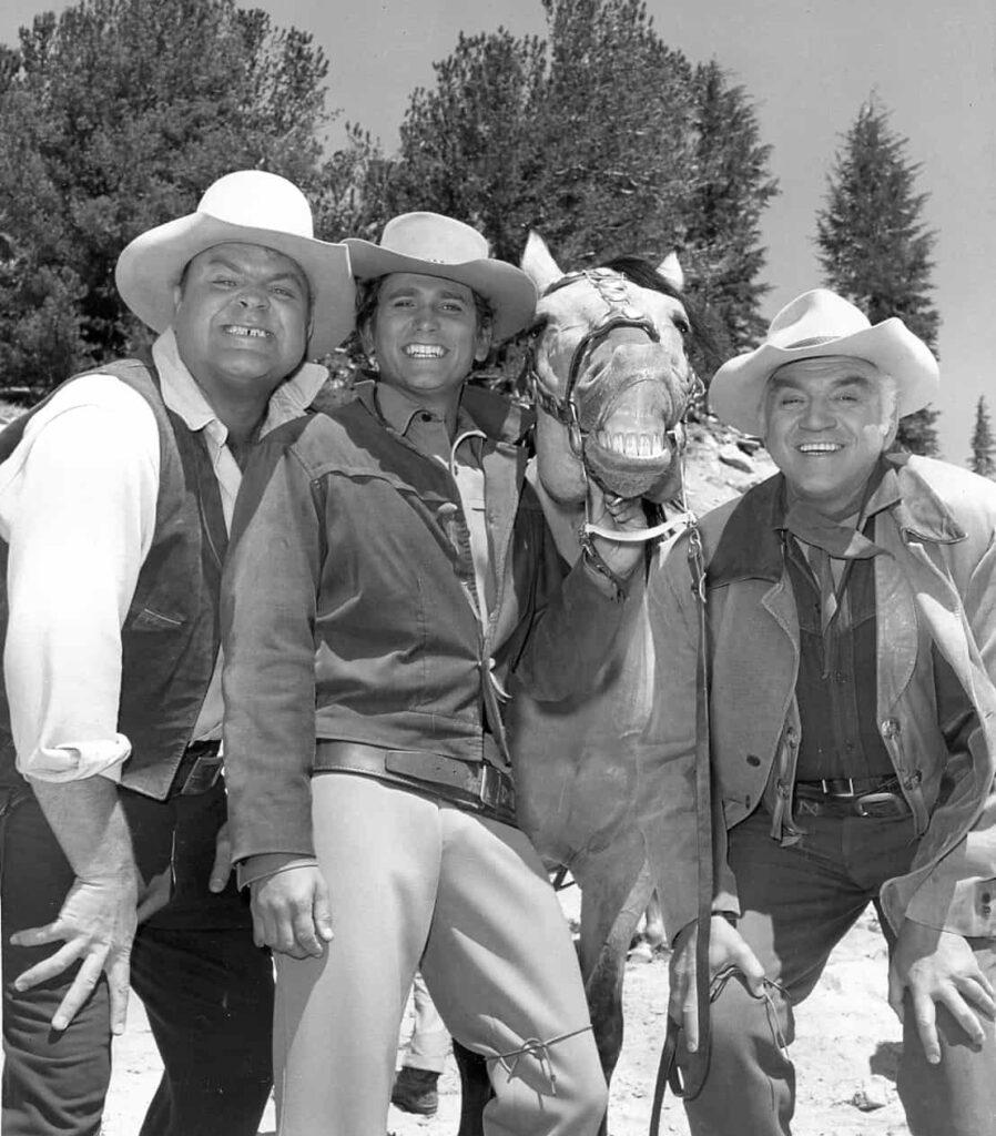 Lorne Greene in seiner Paraderolle des Ben Cartwright (rechts) in der Fernsehserie Bonanza, gemeinsam mit seinen Filmsöhnen (von links) Dan Blocker (Hoss), Michael Landon (Little Joe) sowie Ben's Pferd Buck im Jahr 1968. Foto commons.wikimedia.org/Gemeinfrei