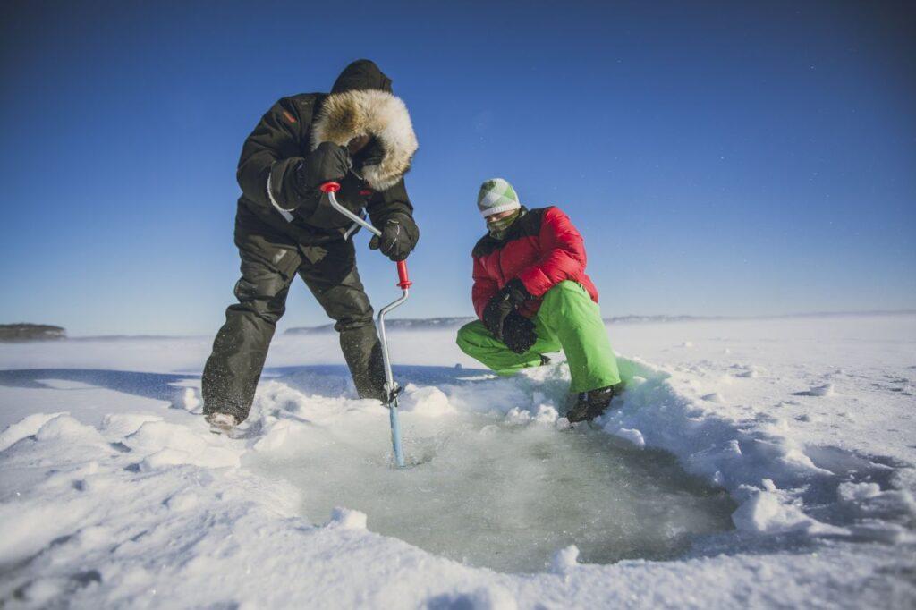 Gut eingepackt für ein winterliches Vergnügen. Eisfischen oder Winter-Fliegenfischen auf Ontarios Seen oder Flüssen. Foto Destination Ontario