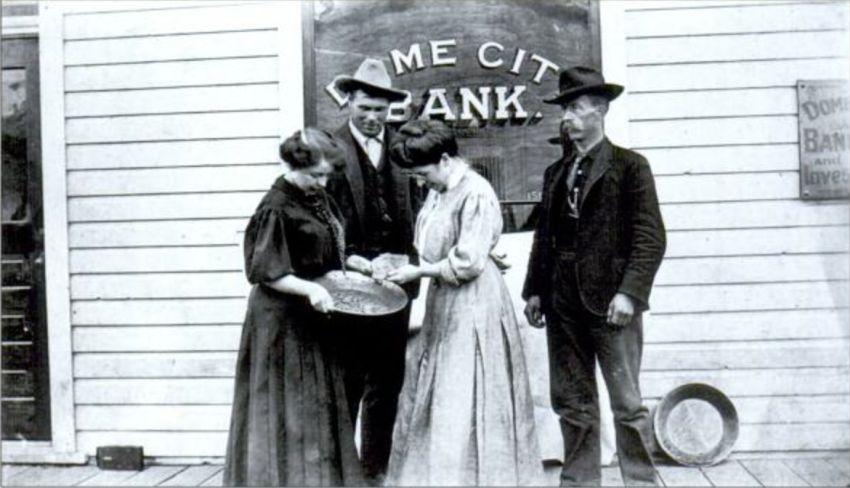 In der Bildmitte stehend betrachtet Belinda Mulrooney vor der Dome-City-Bank ein 88-Unzen-Nugget. Die Aufnahme, die sie mit ihrer Schwester Schwester Margaret Mulrooney sowie ,mit Miller Thosteseu und Jack Tobin zeigt, entstand etwa im Jahr 1905. Foto unbekannter Fotograf / Public Domain